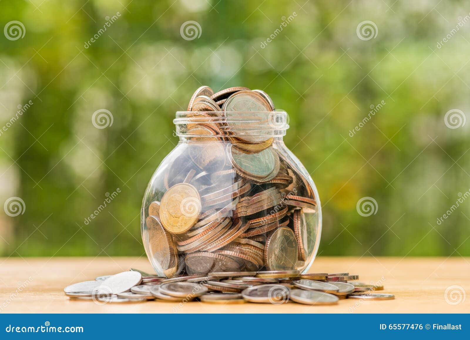 Moedas do baht tailandês que derramam fora do frasco do dinheiro