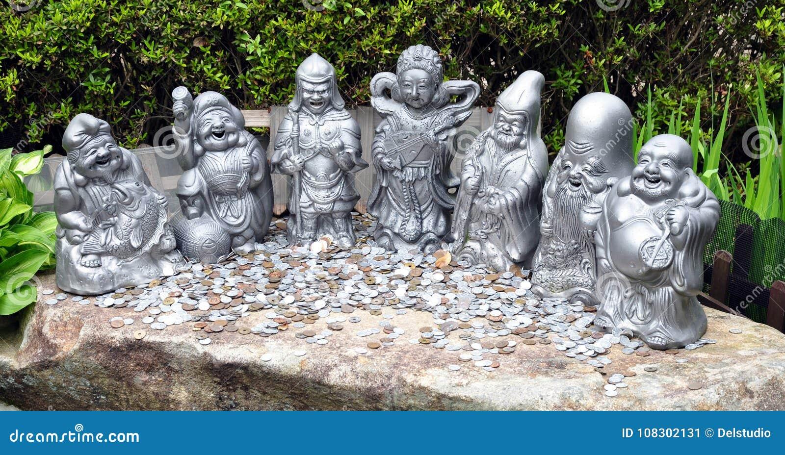 Moedas do dinheiro e sete estátuas afortunadas dos deuses Daisho-no templo, ilha Japão de Miyajima