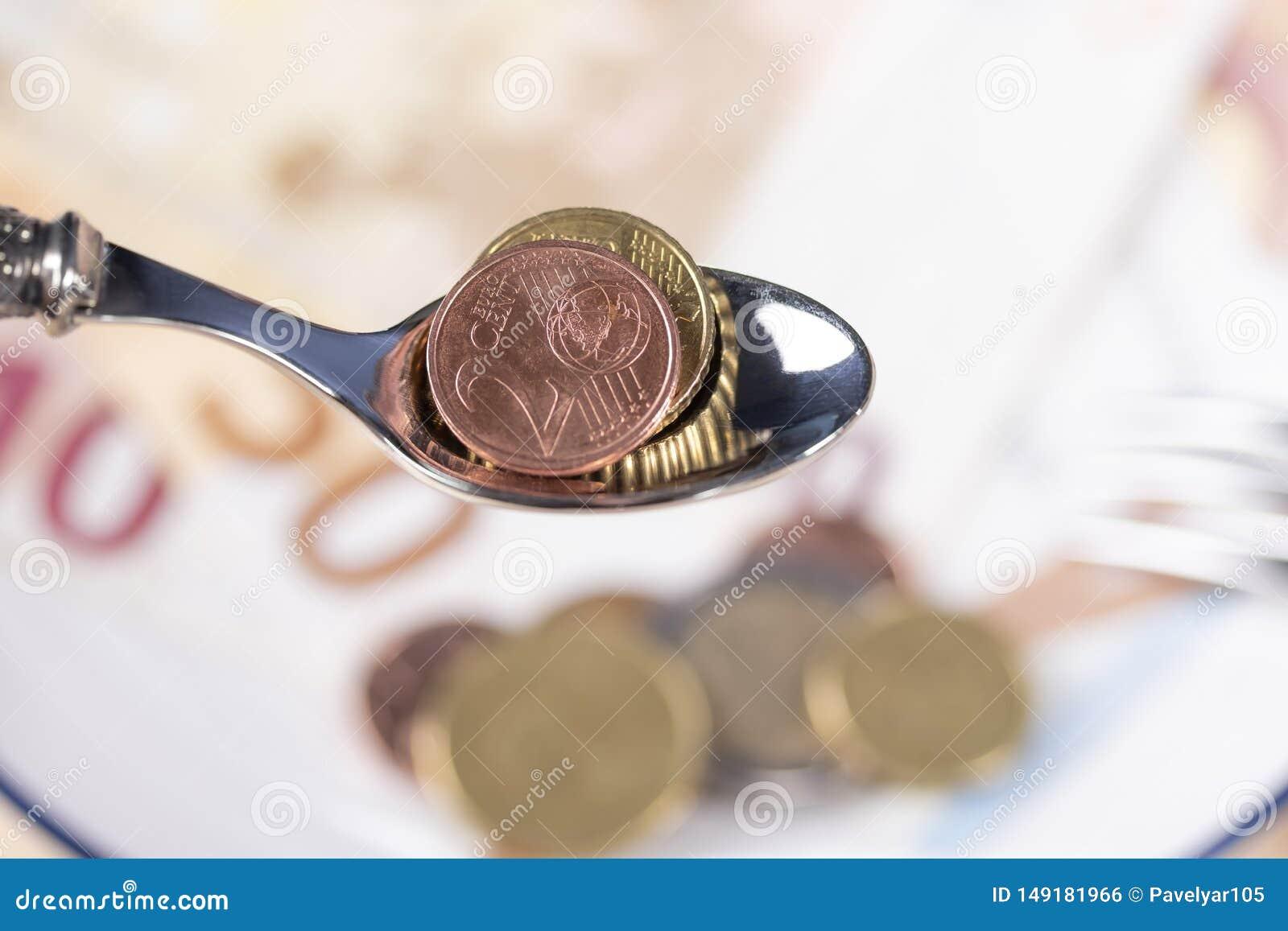 Moedas do Euro em uma colher de sobremesa sobre uma placa do dinheiro com uma beira azul