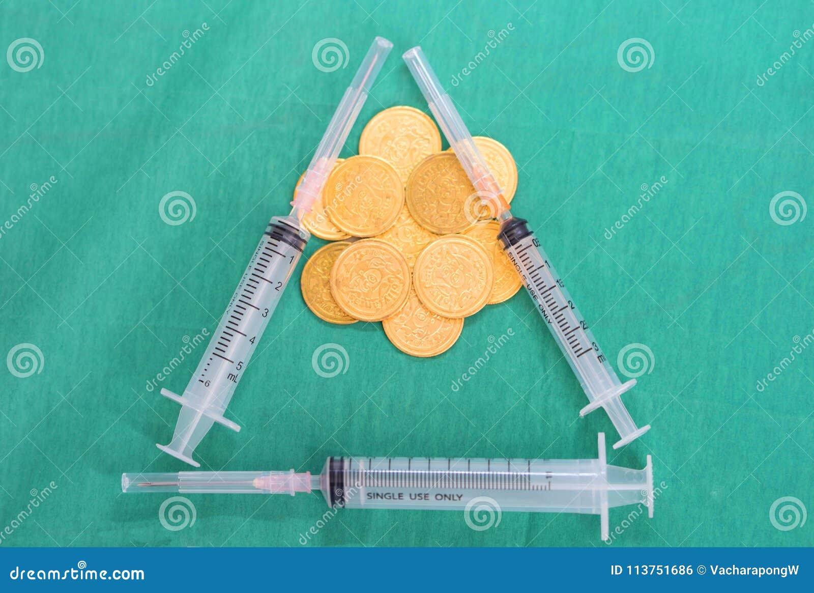 Moedas ou dinheiro com as seringas múltiplas no cov do vestido do verde da cirurgia