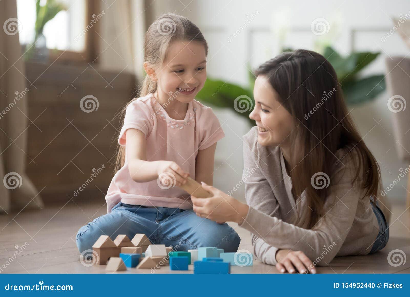 Moeder of babysitterspel met weinig jong geitje met stuk speelgoed blokken