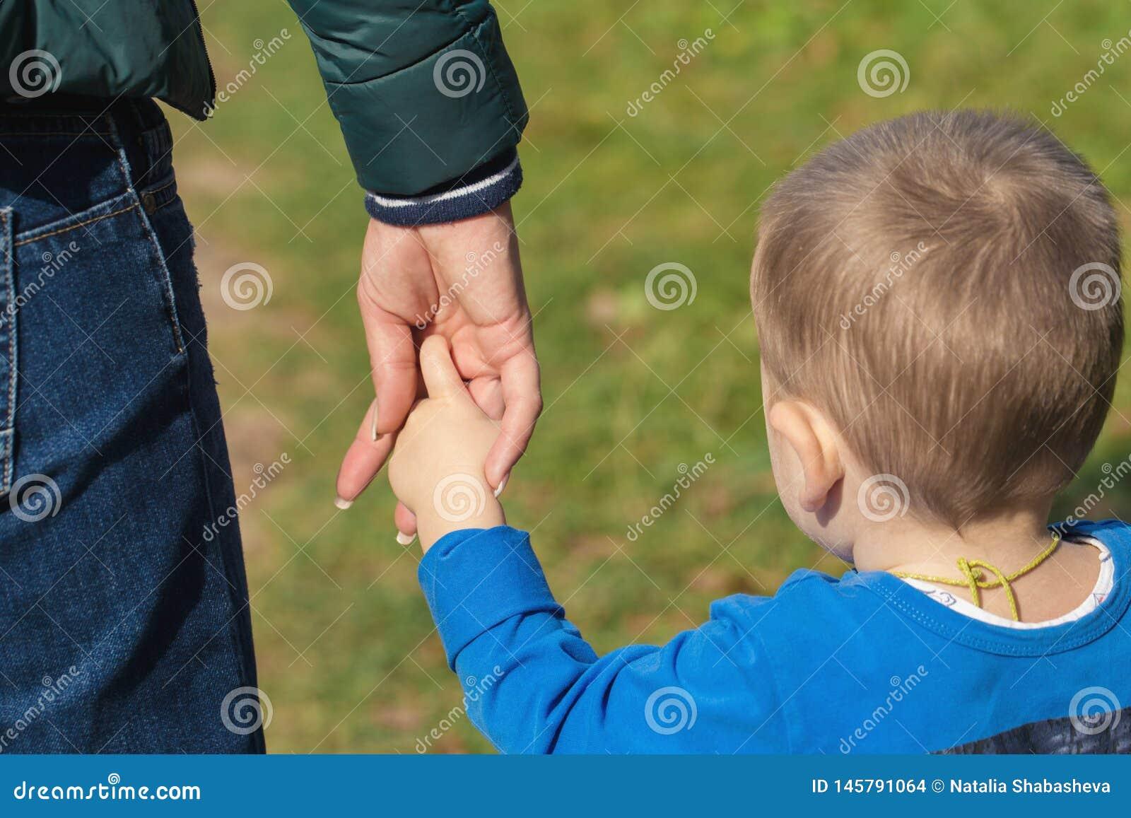 Moeder die een hand van zijn zoon in de zomerdag in openlucht houden