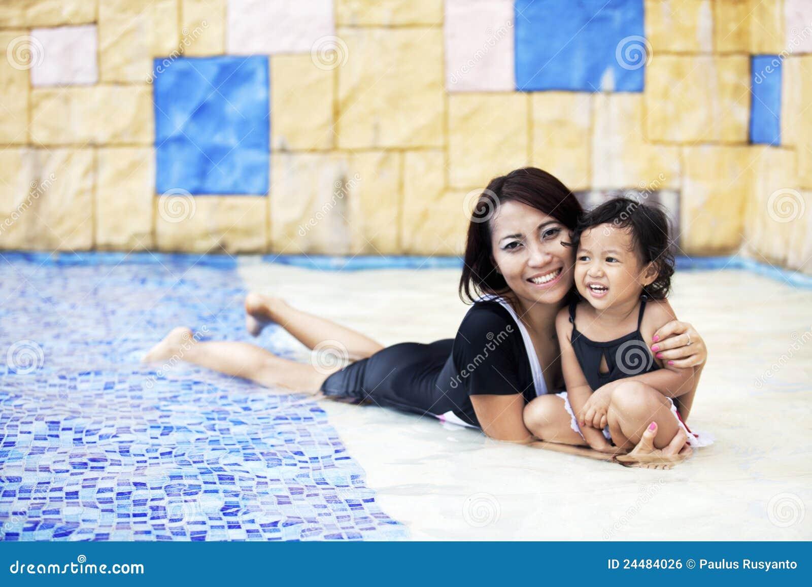 Moeder die een kwaliteitstijd heeft bij zwembad