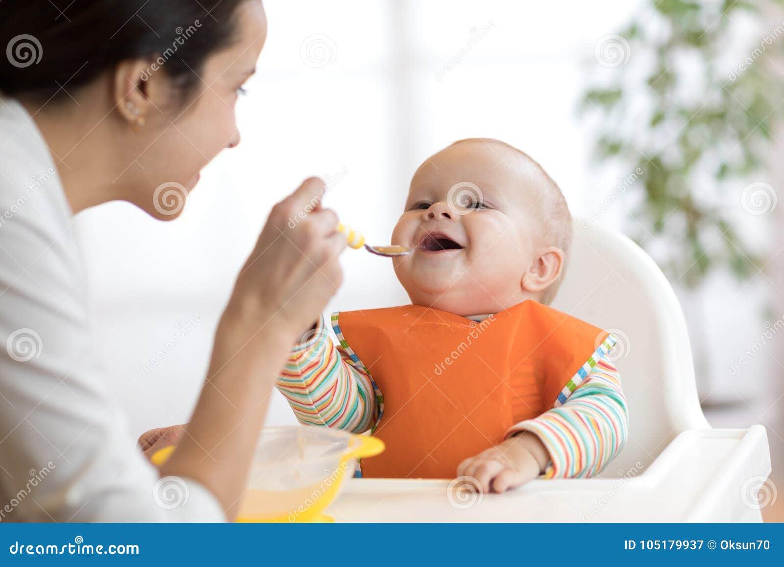 Moeder die haar baby met lepel voeden Moeder die gezond voedsel thuis geven aan haar aanbiddelijk kind