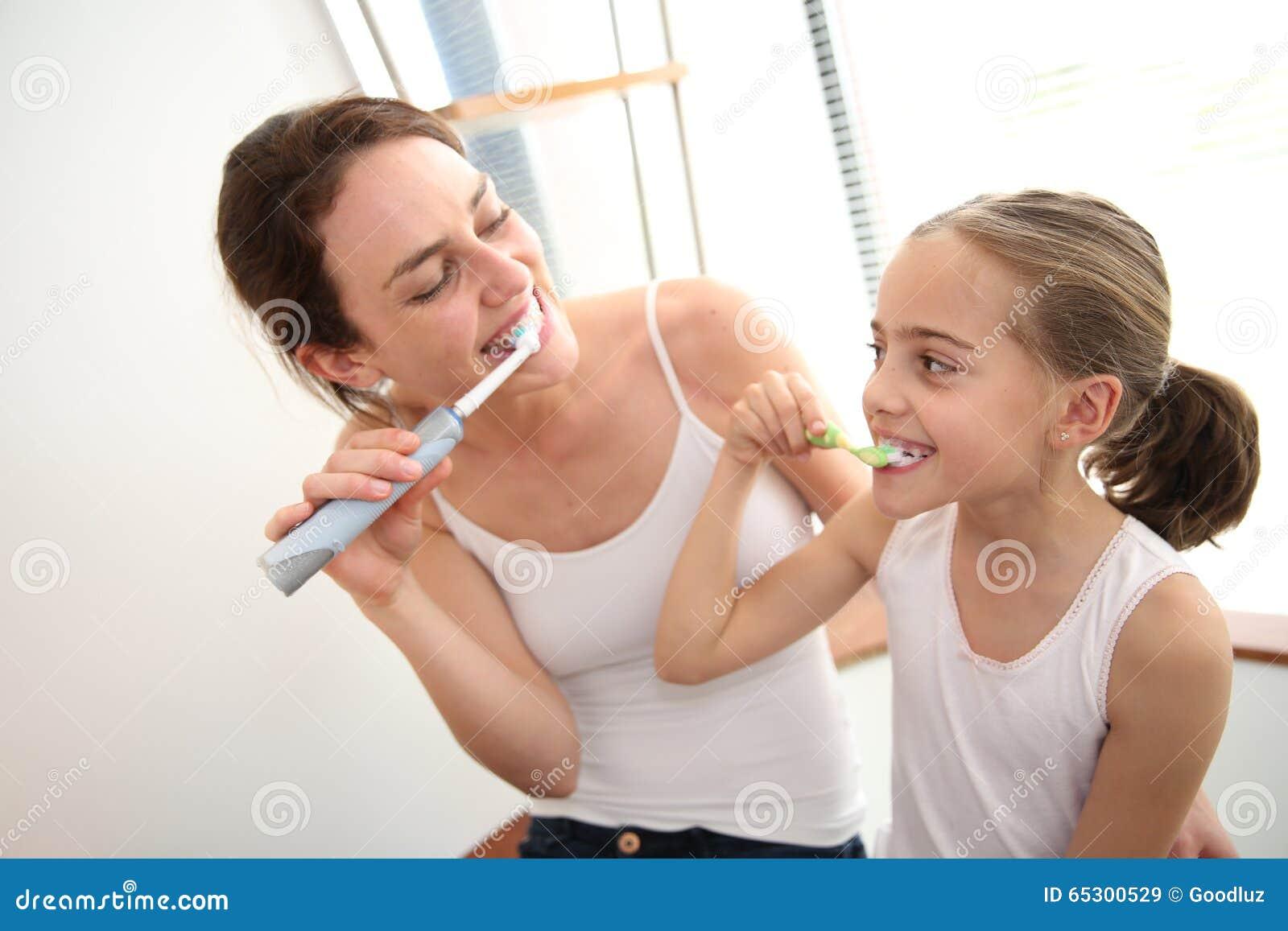 Moeder die haar dochter onderwijzen hoe te om tanden te borstelen