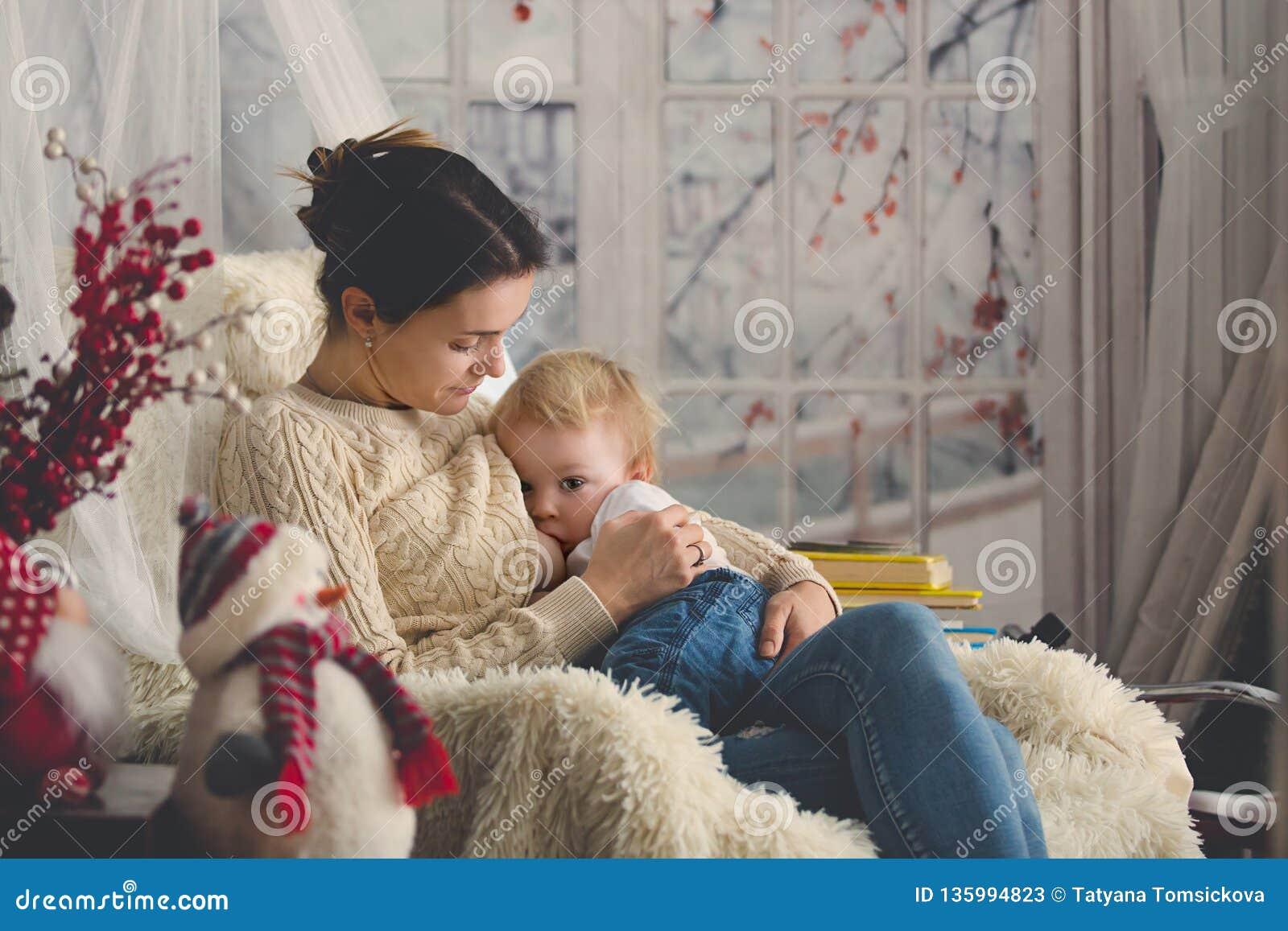 Moeder die haar zitting van de peuterzoon in comfortabele leunstoel de borst geven, wintertijd