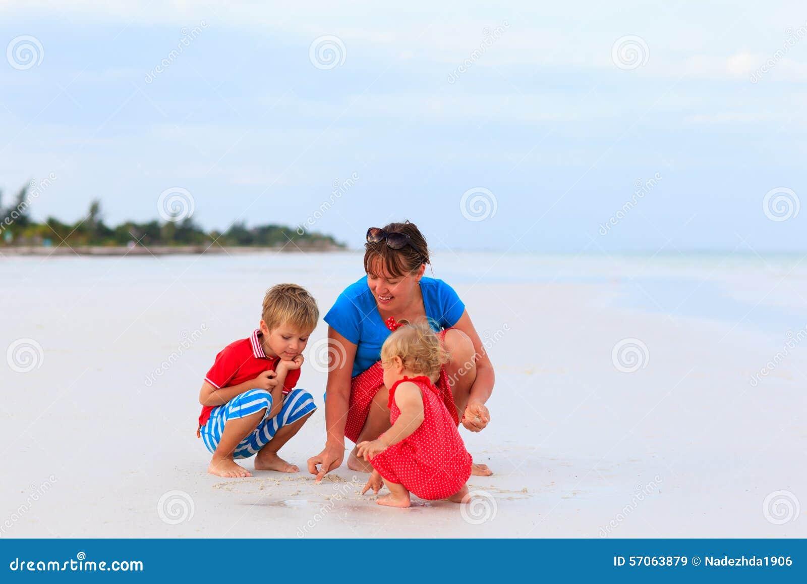 Moeder die met jonge geitjes op strand spelen