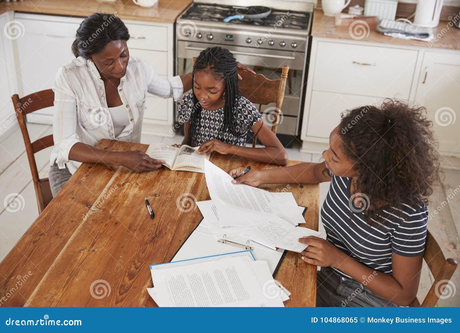 Moeder die Twee Dochters helpen die bij Lijst zitten die Thuiswerk doen