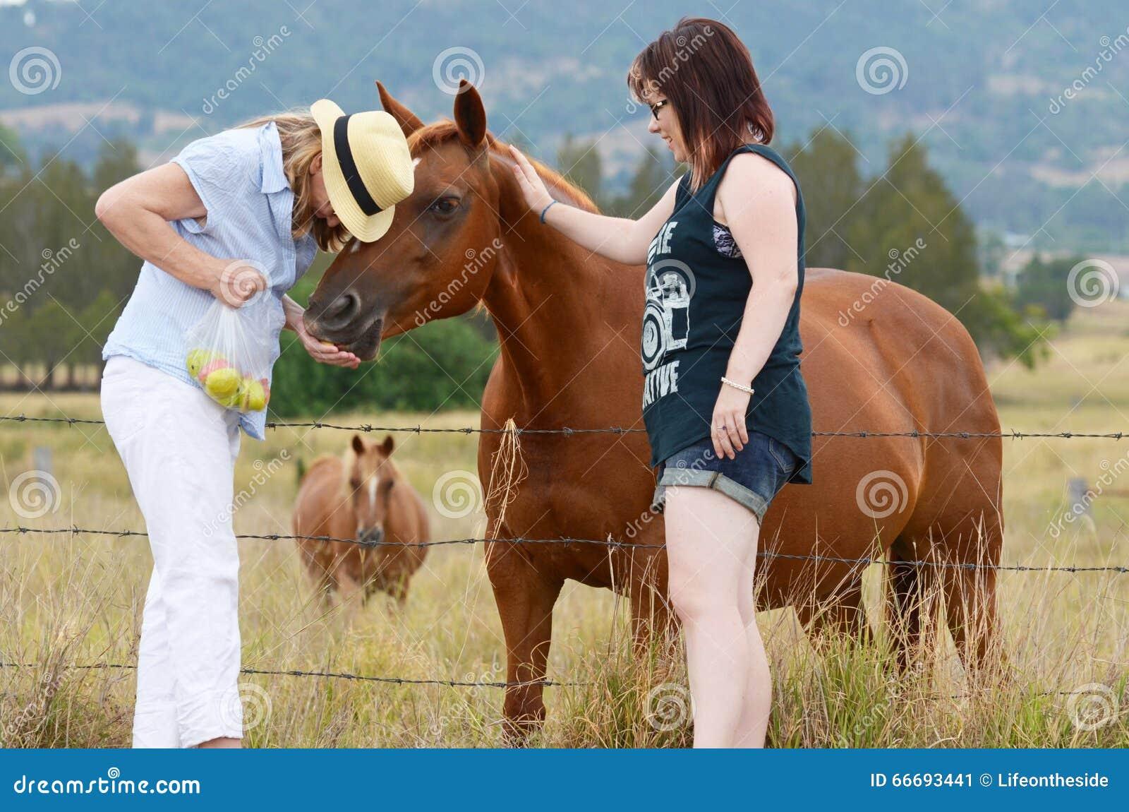 Moeder & dochter die van dag genieten die samen paarden in land voeden