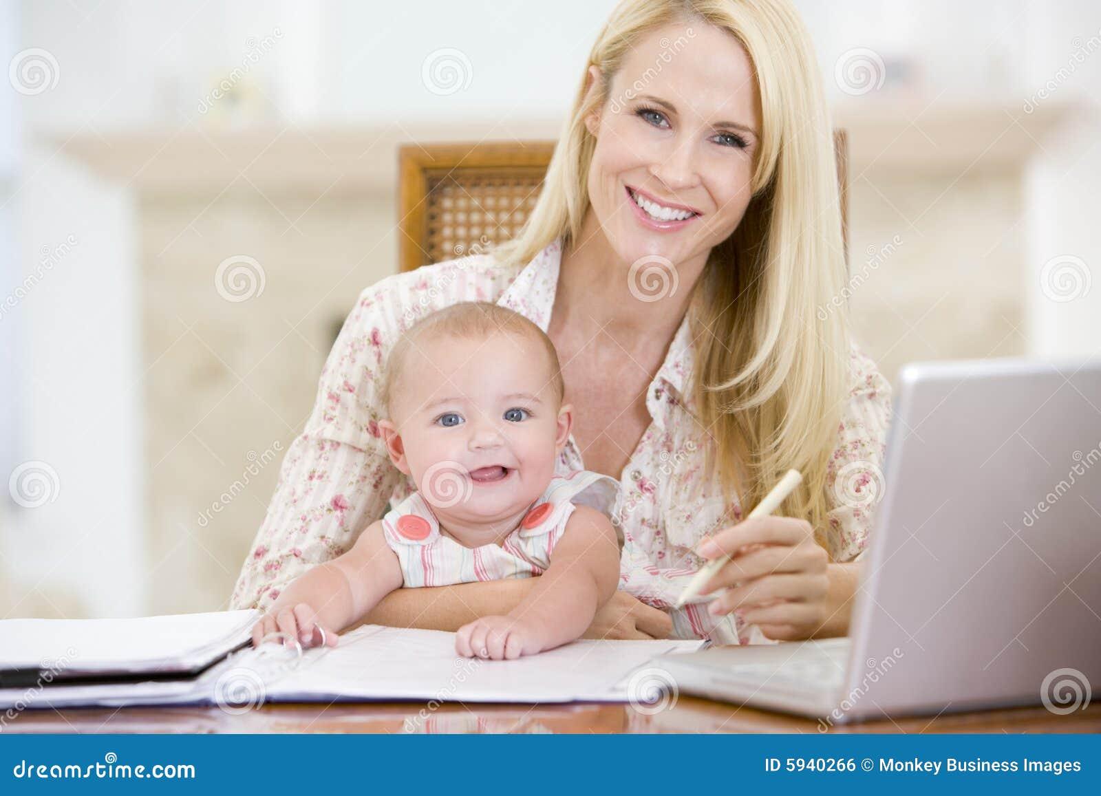 Moeder en baby in eetkamer met laptop