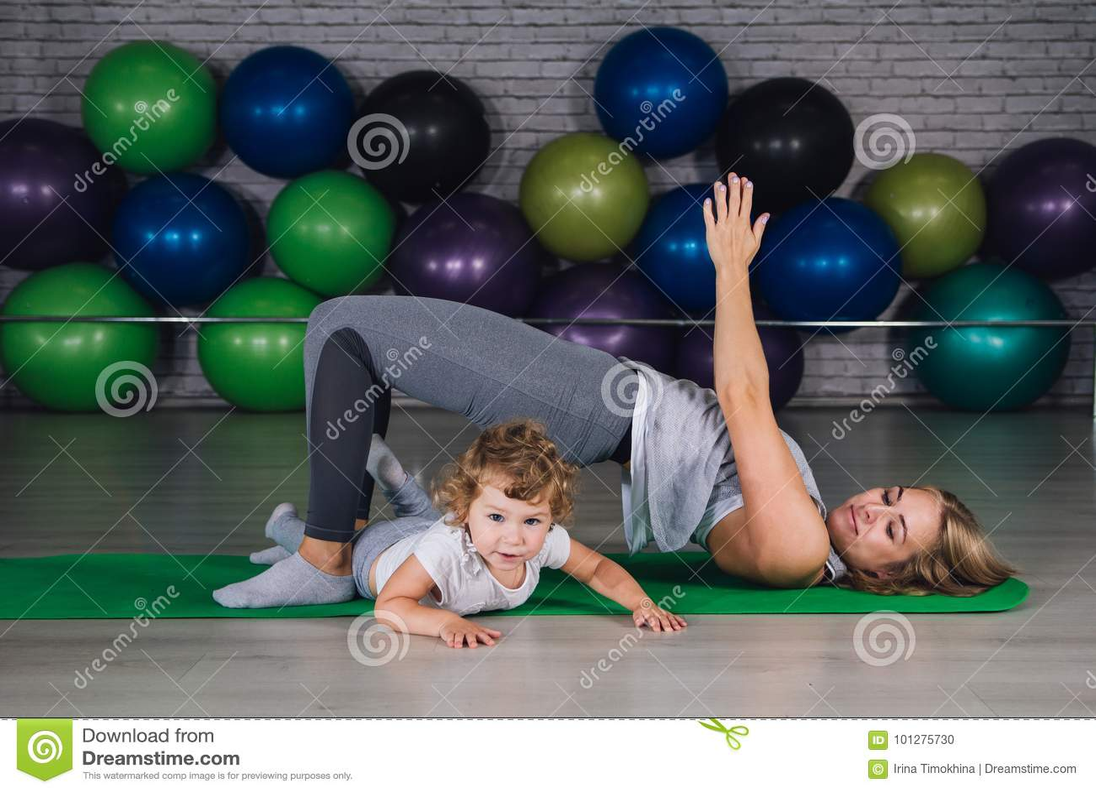 Moeder en baby girl do exercises samen in de gymnastiek