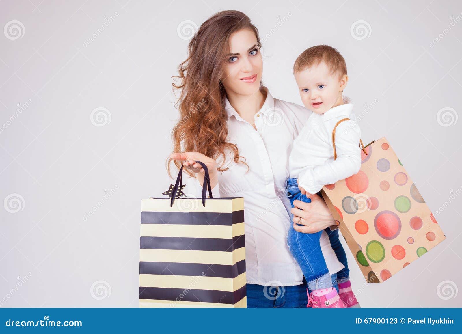 Moeder en babyholdingszakken met aankopen en speelgoed