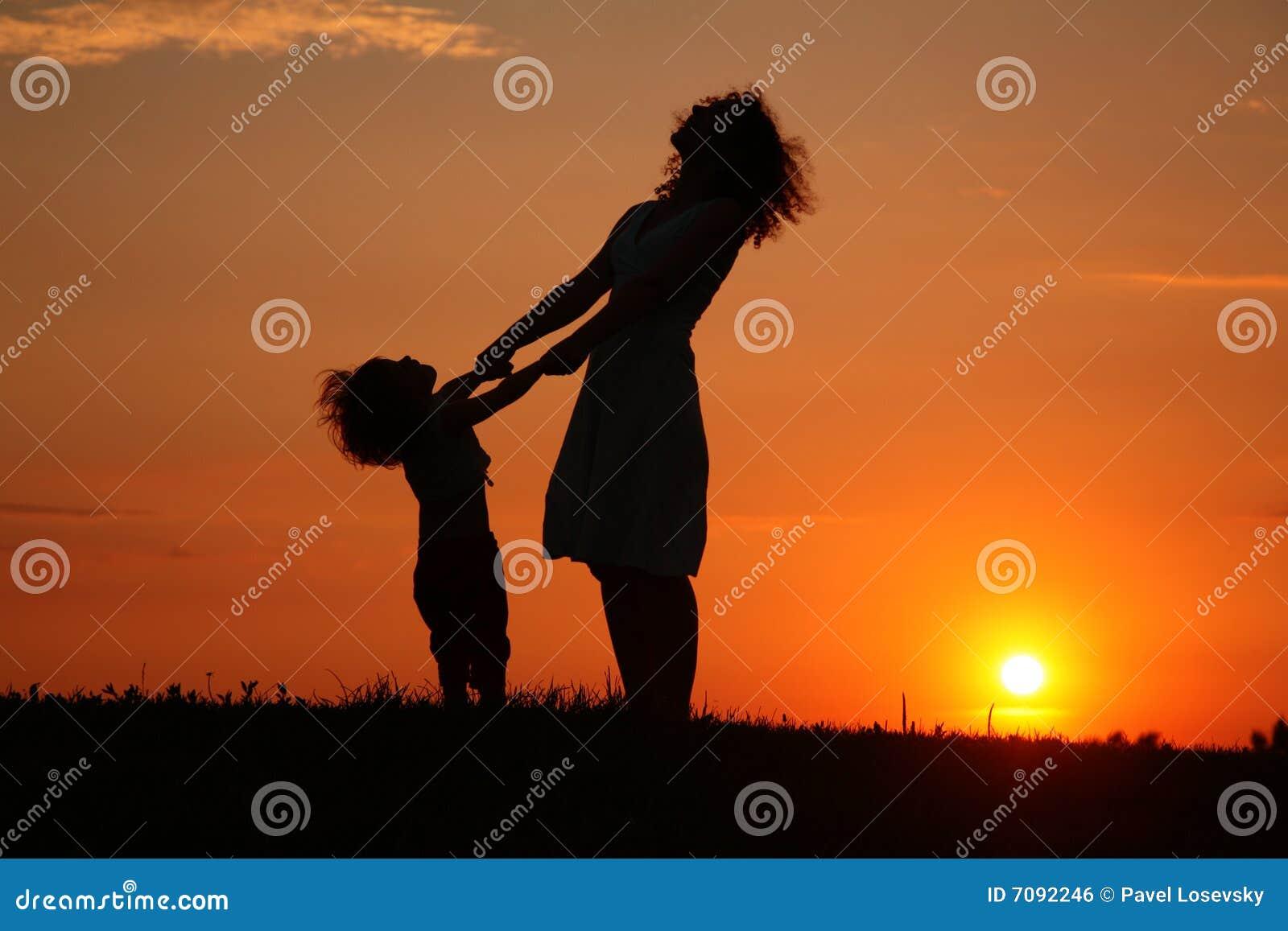 Moeder en dochter bij zonsondergang het letten op op hemel