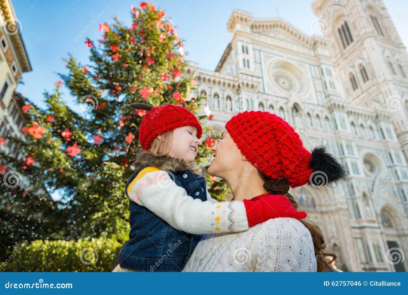 Moeder en dochter die dichtbij Kerstboom in Florence koesteren