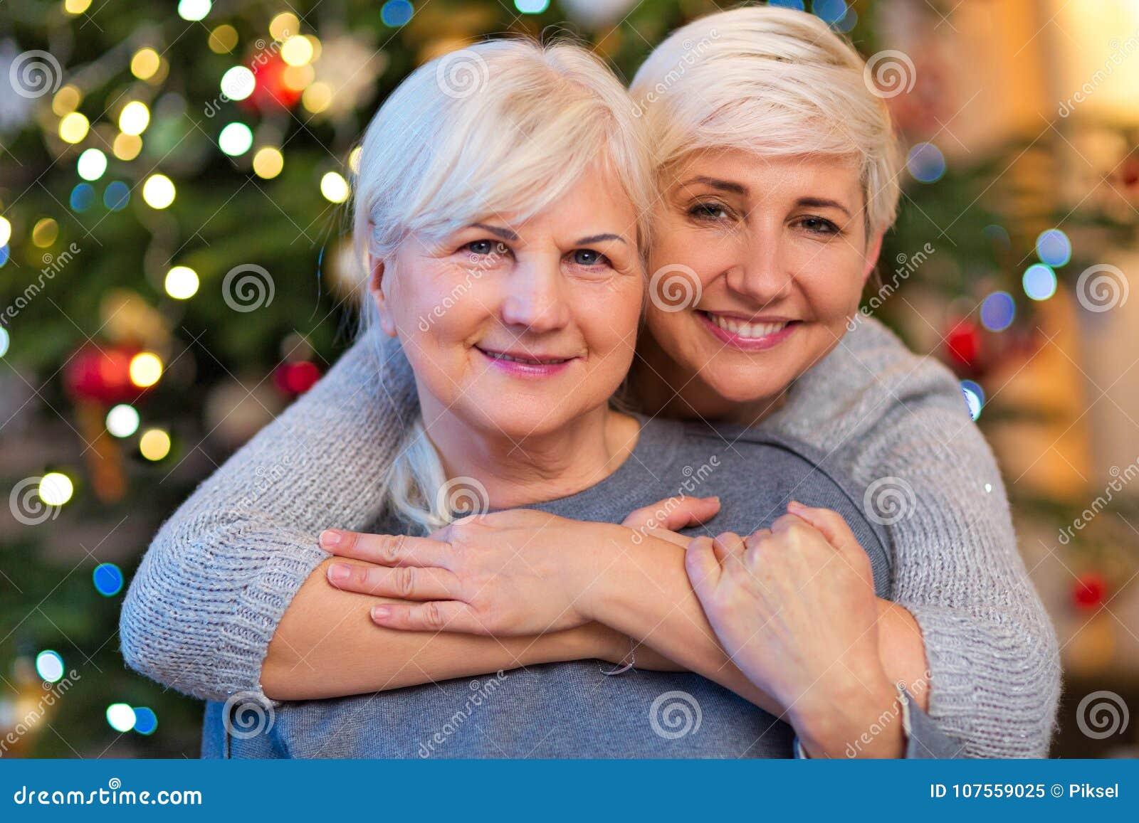 Moeder en dochter die door Kerstboom koesteren