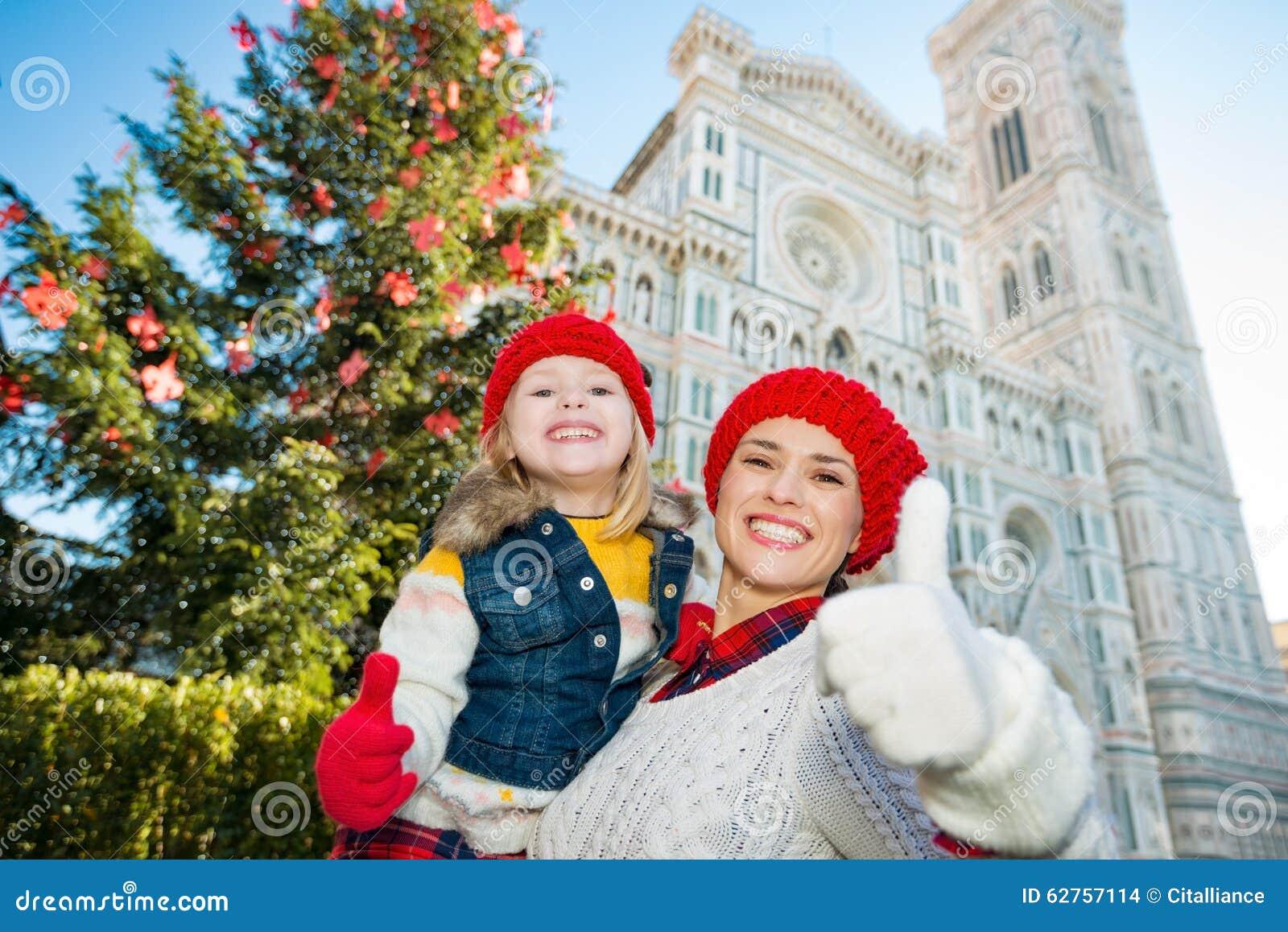Moeder en dochter die duimen in Kerstmis Florence tonen