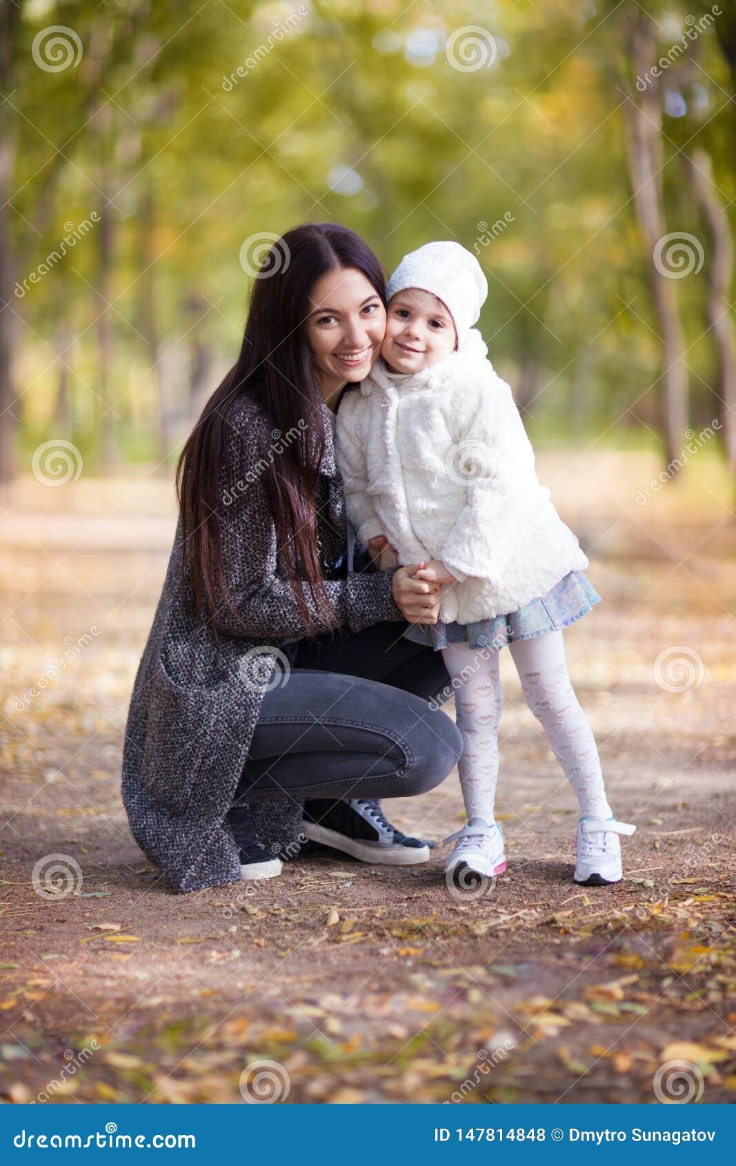 Moeder en dochter die in het de herfstpark lopen De scène van de schoonheidsaard met kleurrijke achtergrond, gele bomen en blader