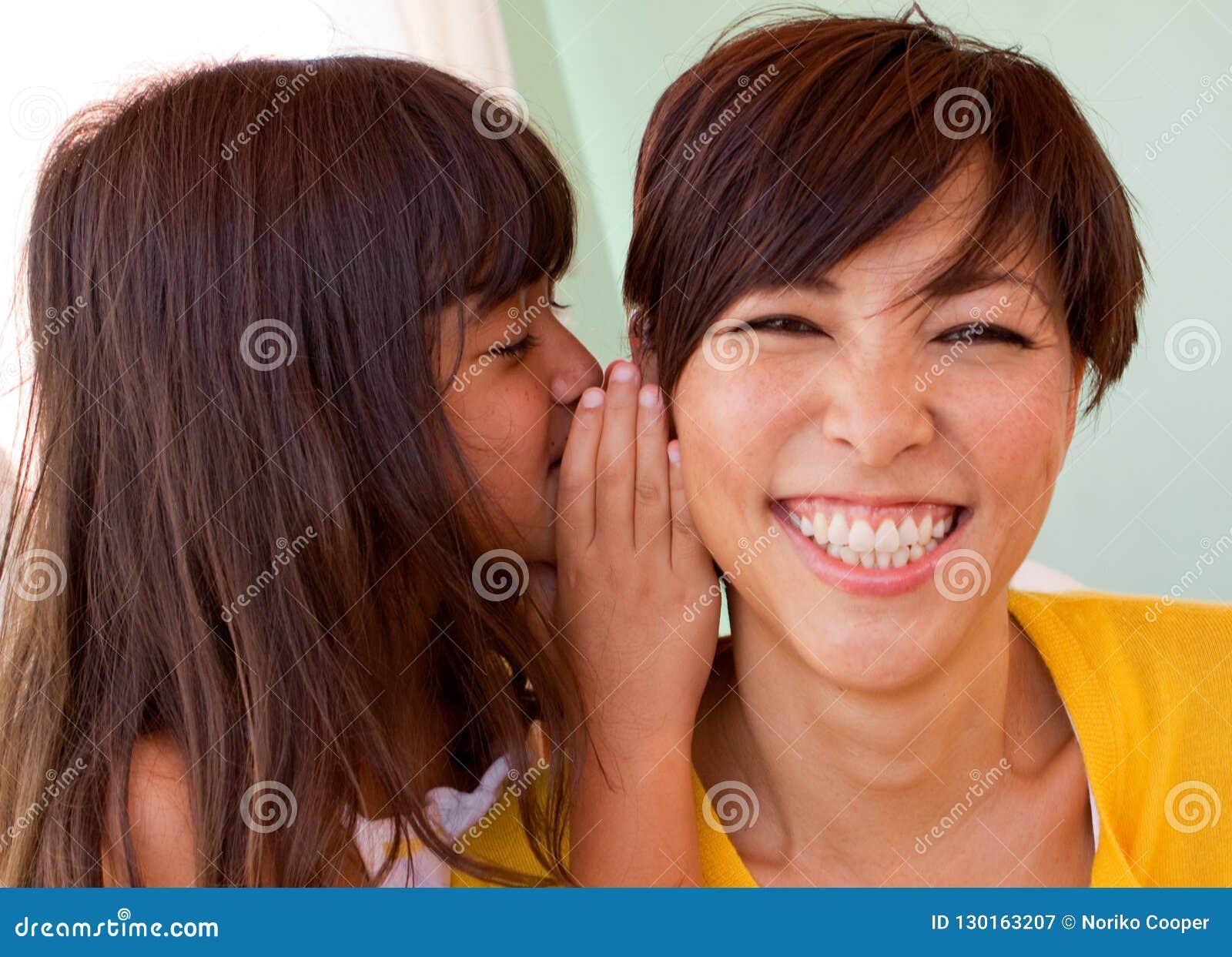 Moeder en dochter die en het vertellen geheimen glimlachen