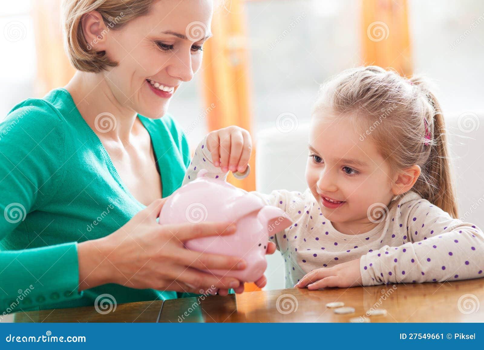 Moeder en dochter die muntstukken zetten in spaarvarken
