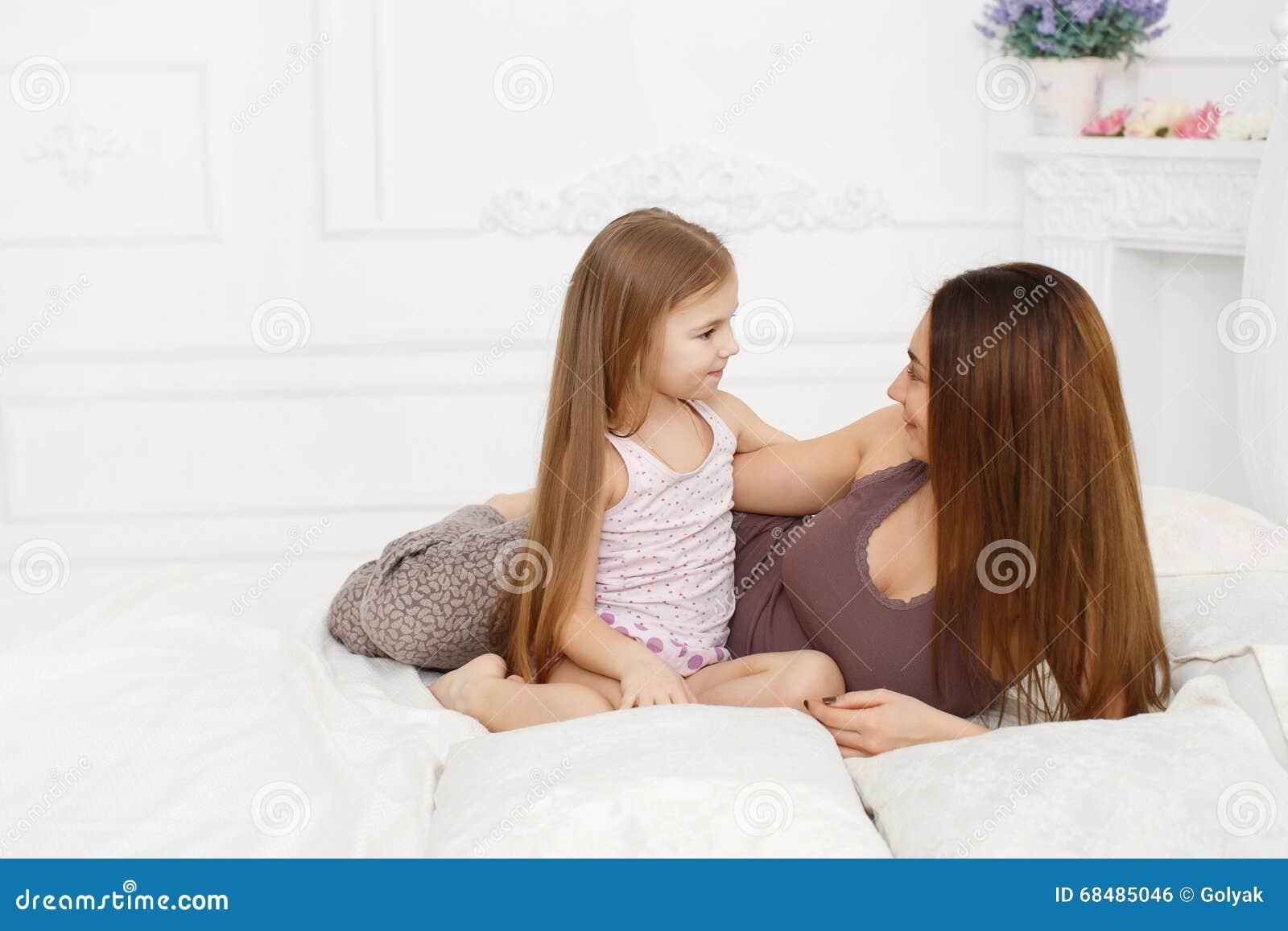 Moeder en dochter die op een wit bed liggen stock foto afbeelding 68485046 - Wit bed capitonne ...