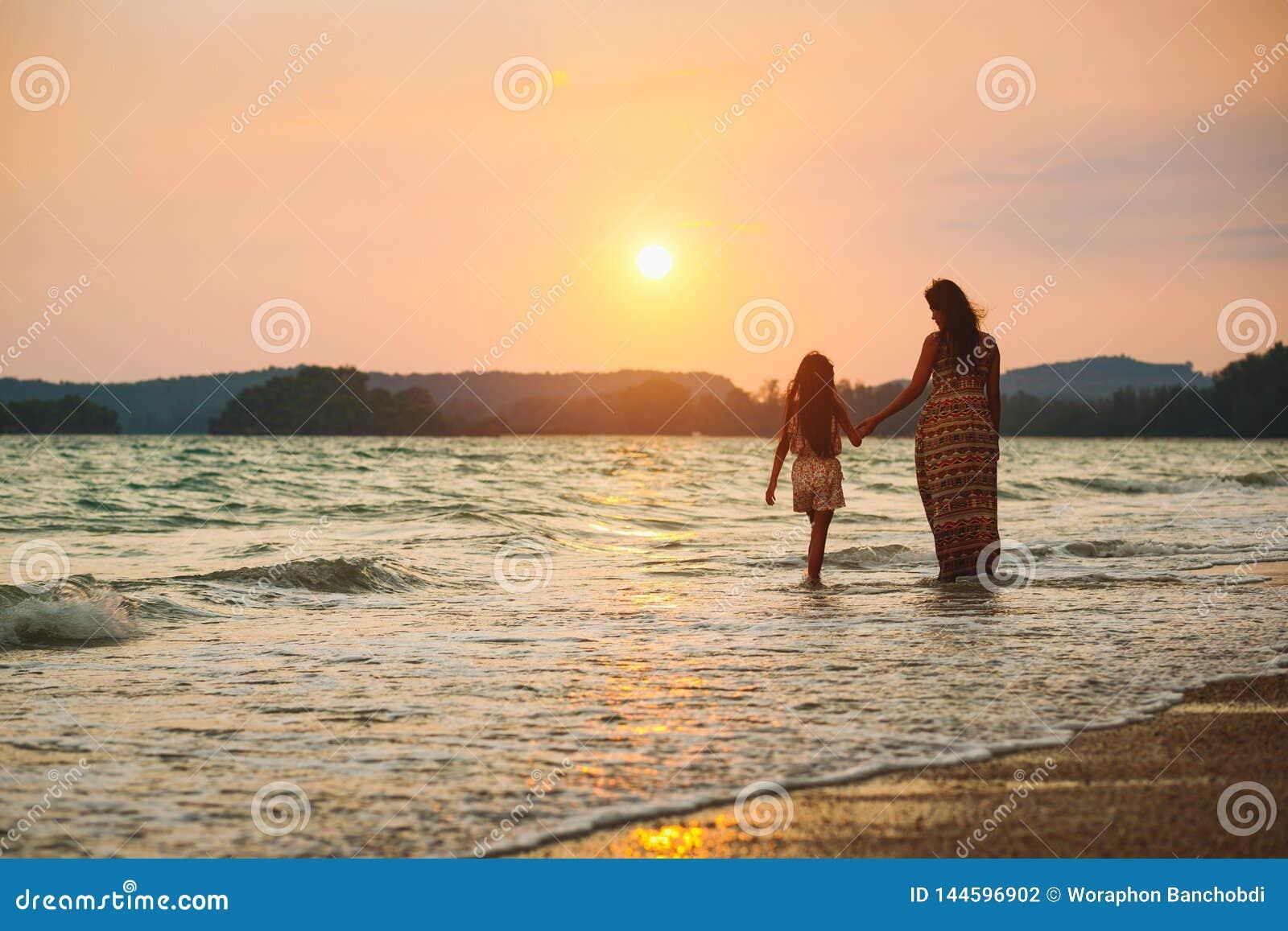 Moeder en dochter die op het strand met zonsondergang lopen