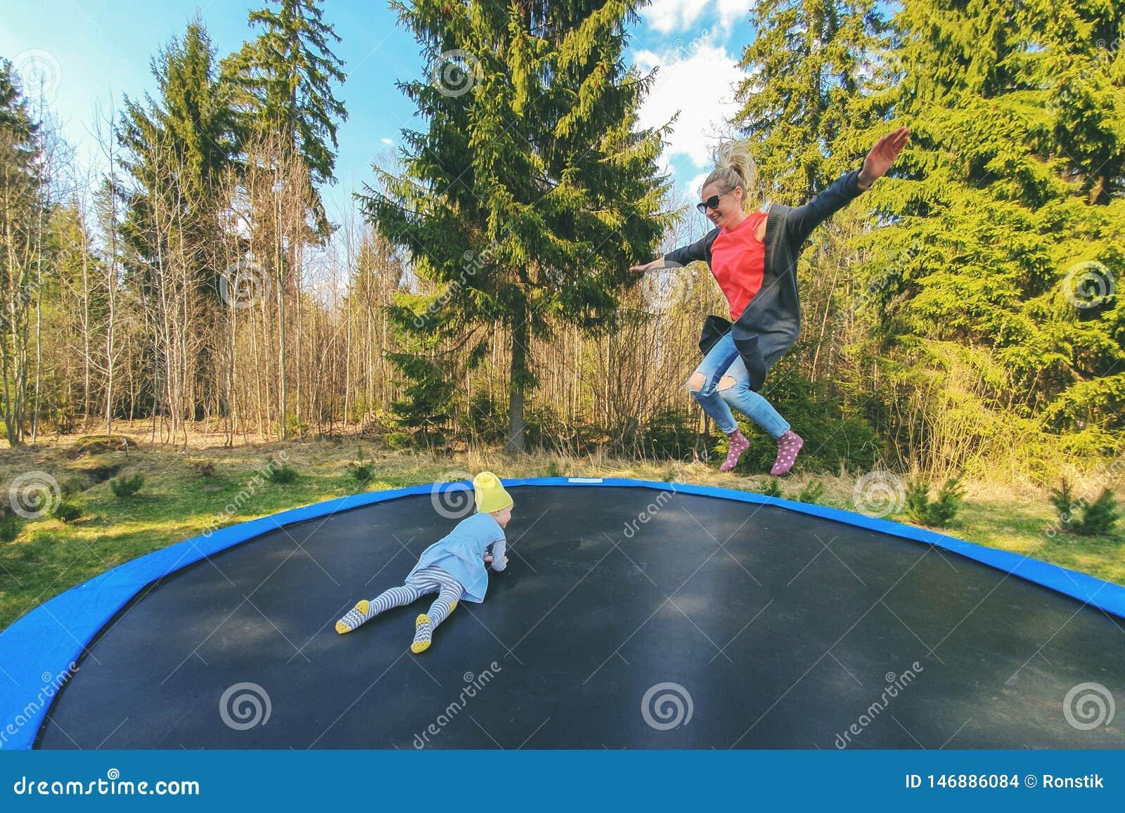 Moeder en dochter die op trampoline in openlucht springen
