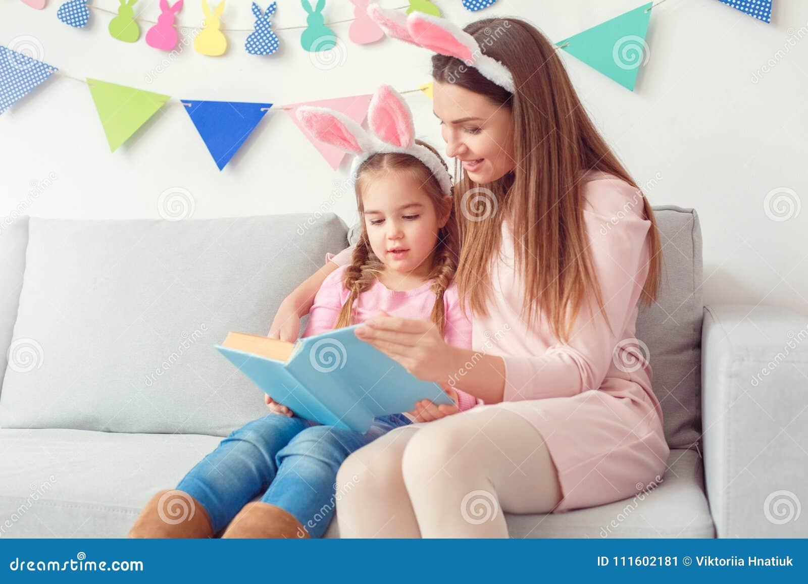 Moeder en dochter in weekend die van konijntjesoren samen het thuis zitten
