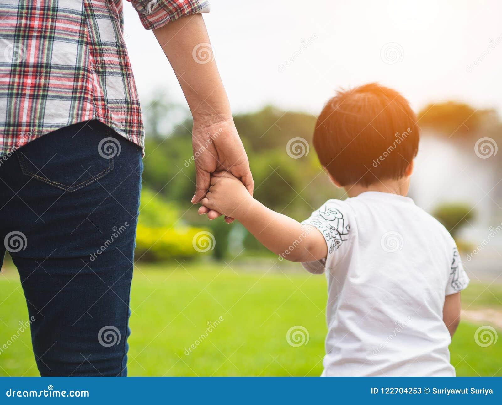Moeder en dochterholdingshanden die in het park lopen Jong geitje en M