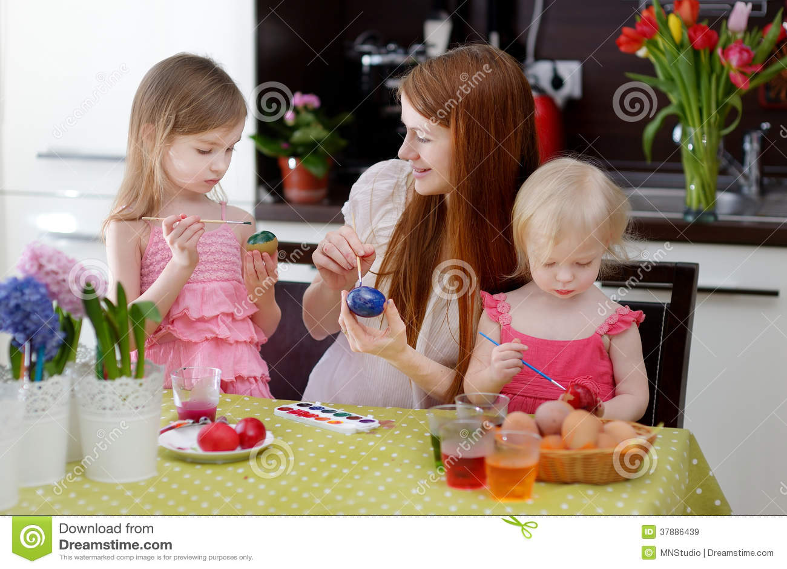 Moeder en haar dochters die paaseieren schilderen