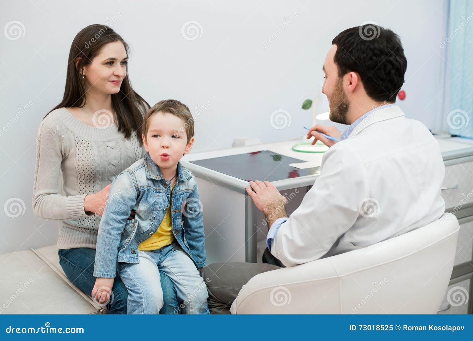 Moeder en haar zoon met grappig gezicht bij het ziekenhuis die aan een arts spreken