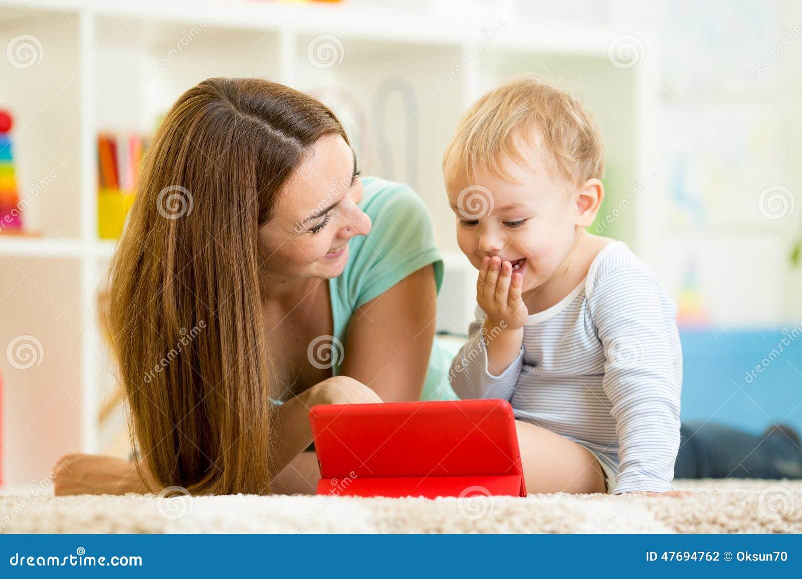 Moeder en jong geitjespel bij tabletcomputer