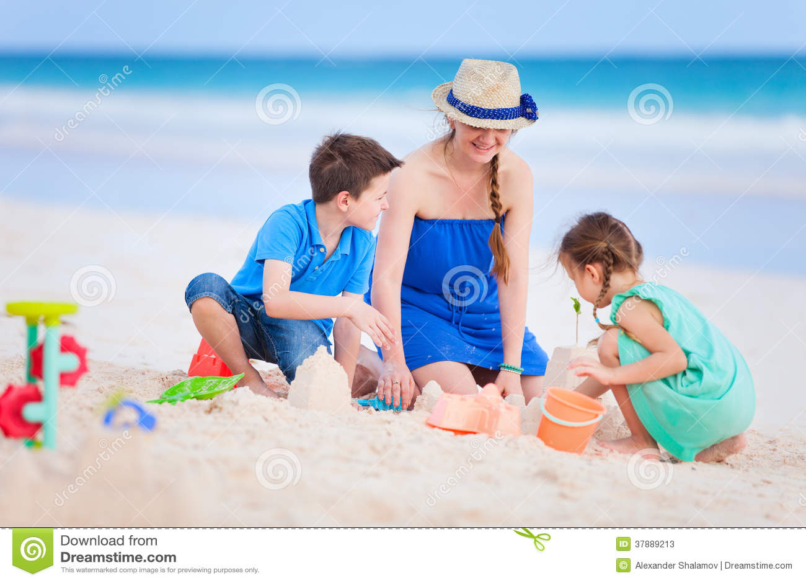 Moeder en jonge geitjes die bij strand spelen