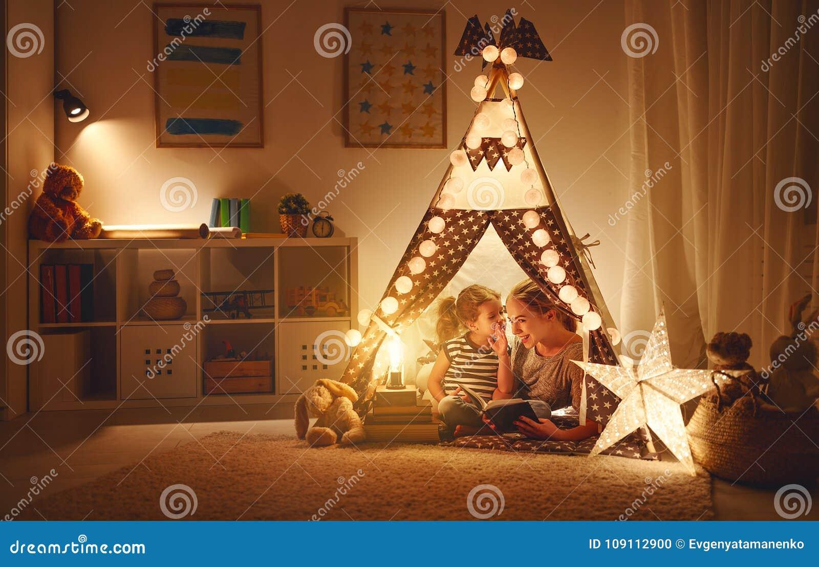 Moeder en kind de dochter met een boek en een flitslicht vóór gaan