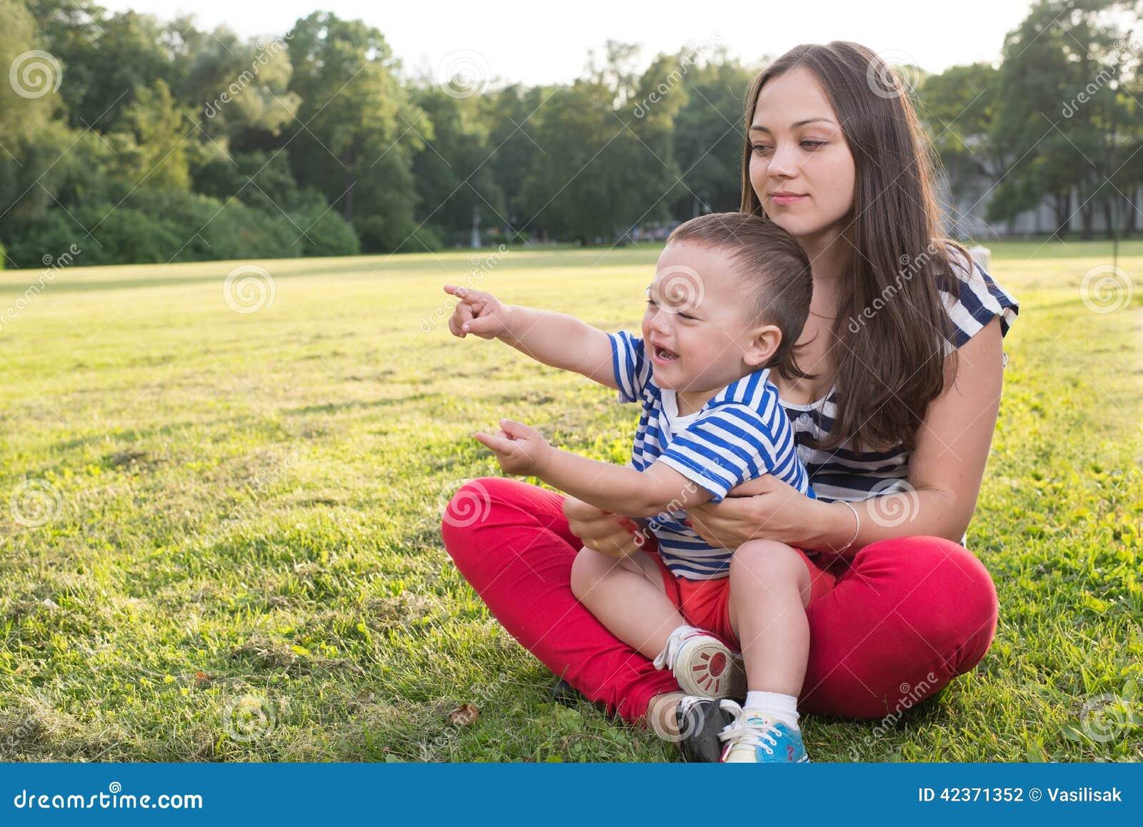 Moeder en kind het spelen bij het gras ongehoorzame jongen en en punt die door zijn vinger schreeuwen