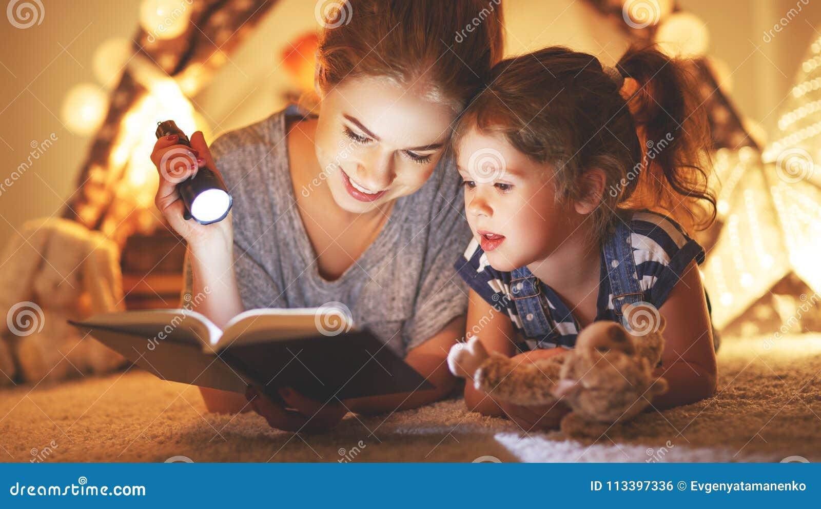 Moeder en kinddochter die een boek en een flitslicht voordien lezen