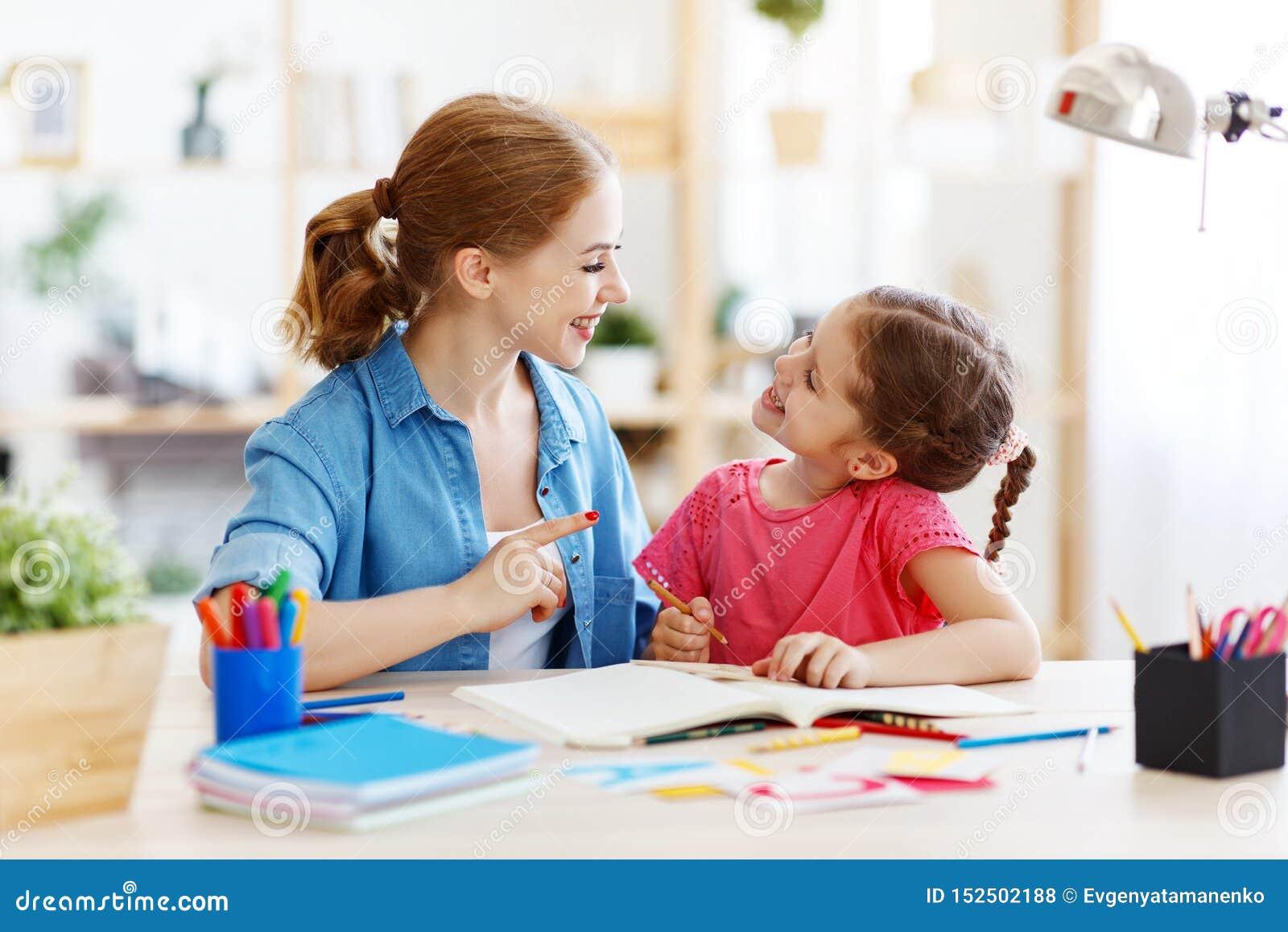 Moeder en kinddochter die en thuiswerk doen die schrijven lezen