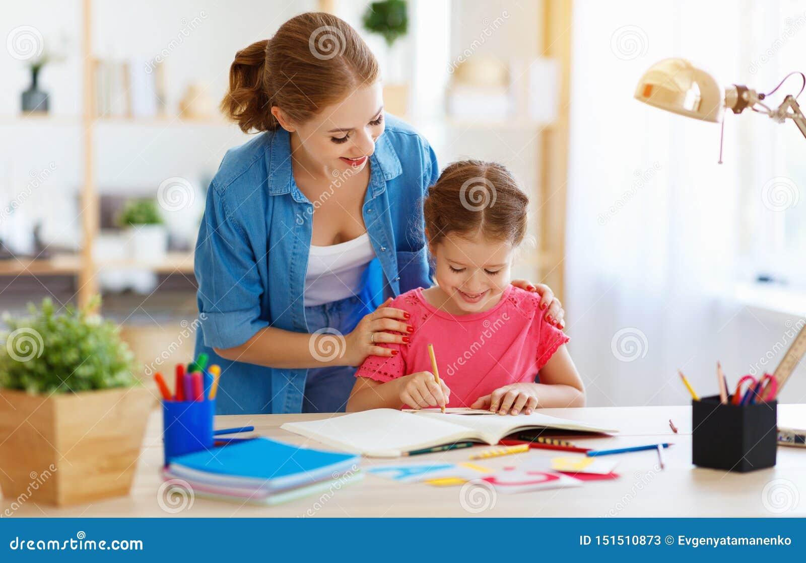 Moeder en kinddochter die thuiswerkaardrijkskunde met bol doen