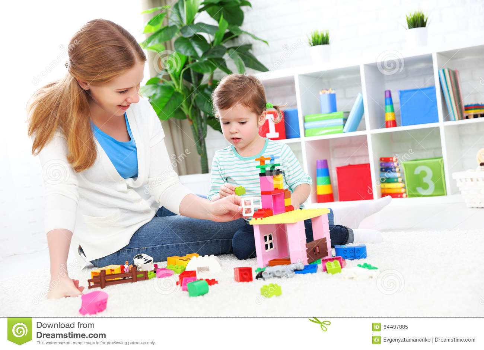 Moeder en kinddochter het spelen, bouwt van aannemer