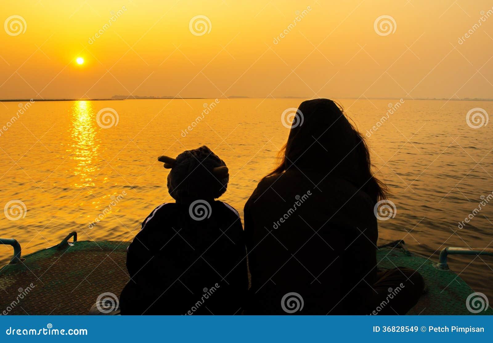 Moeder en kinderensilhouet in de zonsondergang