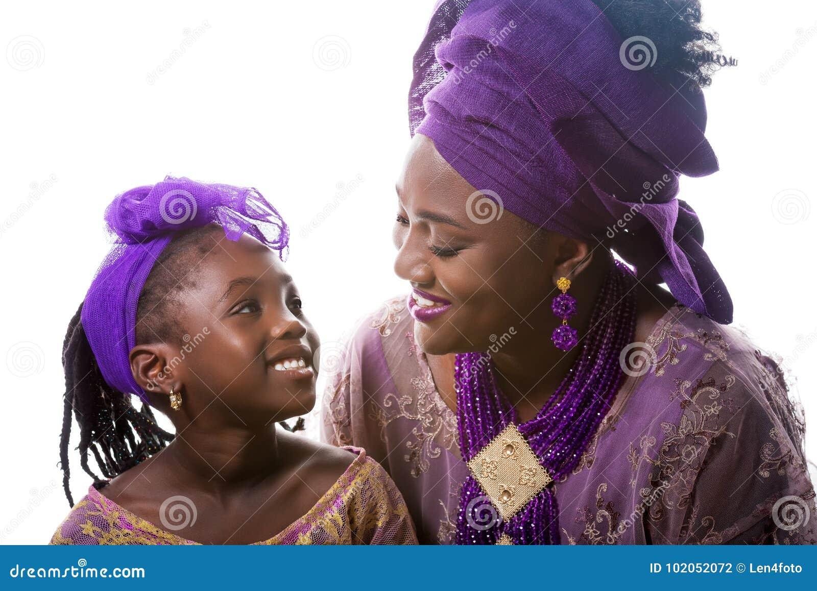 Moeder en kindmeisje die aan elkaar kijken Afrikaanse traditionele kleding