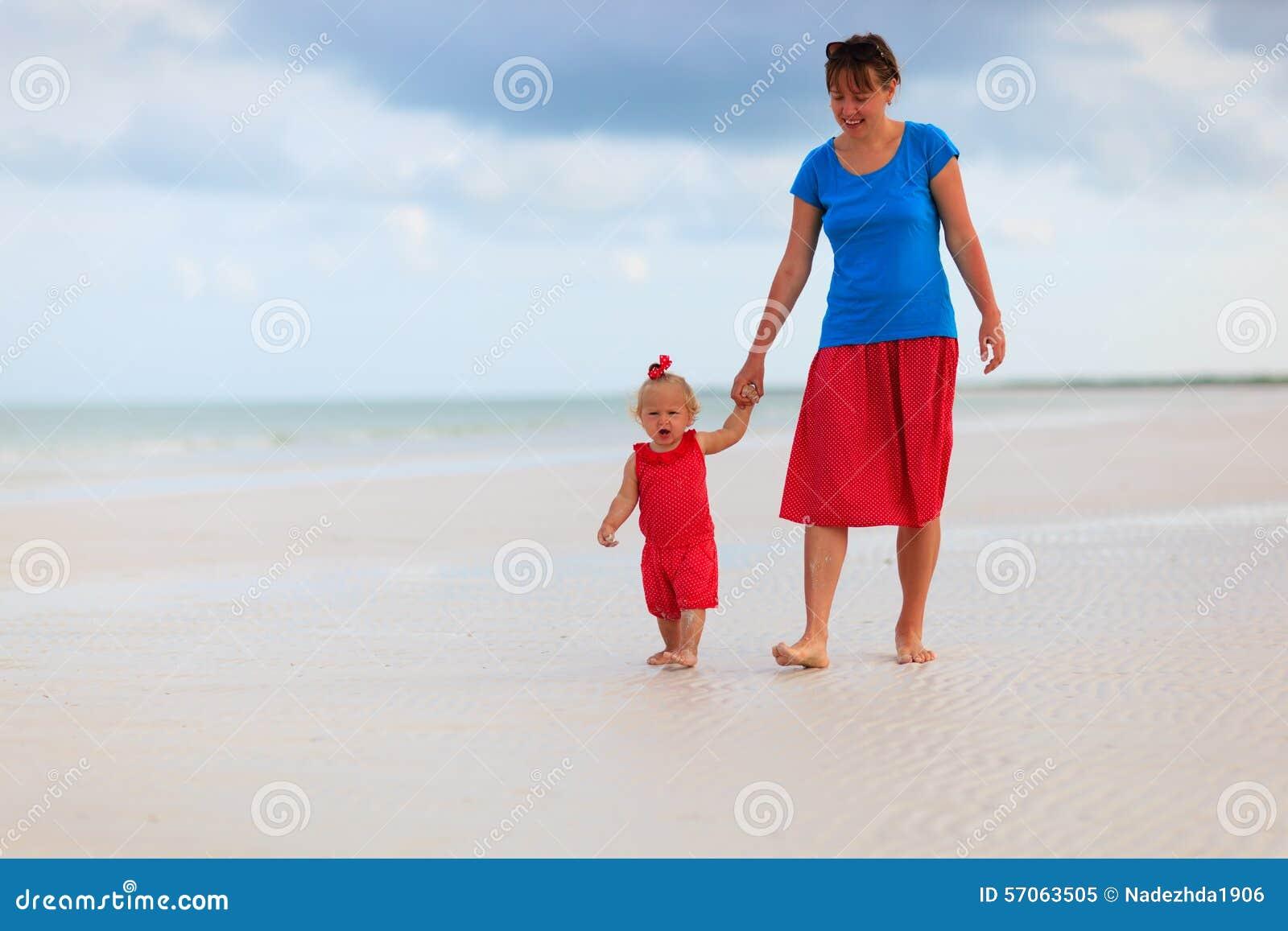 Moeder en weinig dochter die op het strand lopen