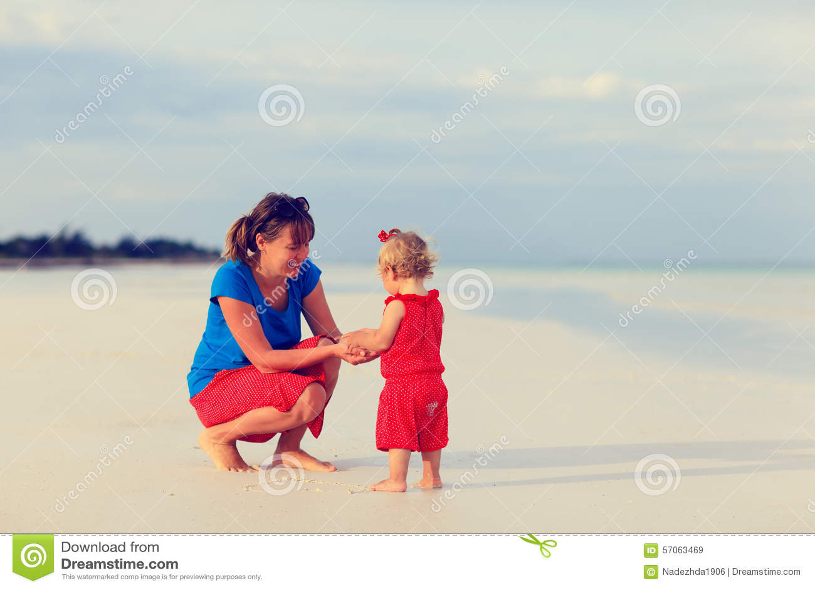 Moeder en weinig dochter op de zomerstrand