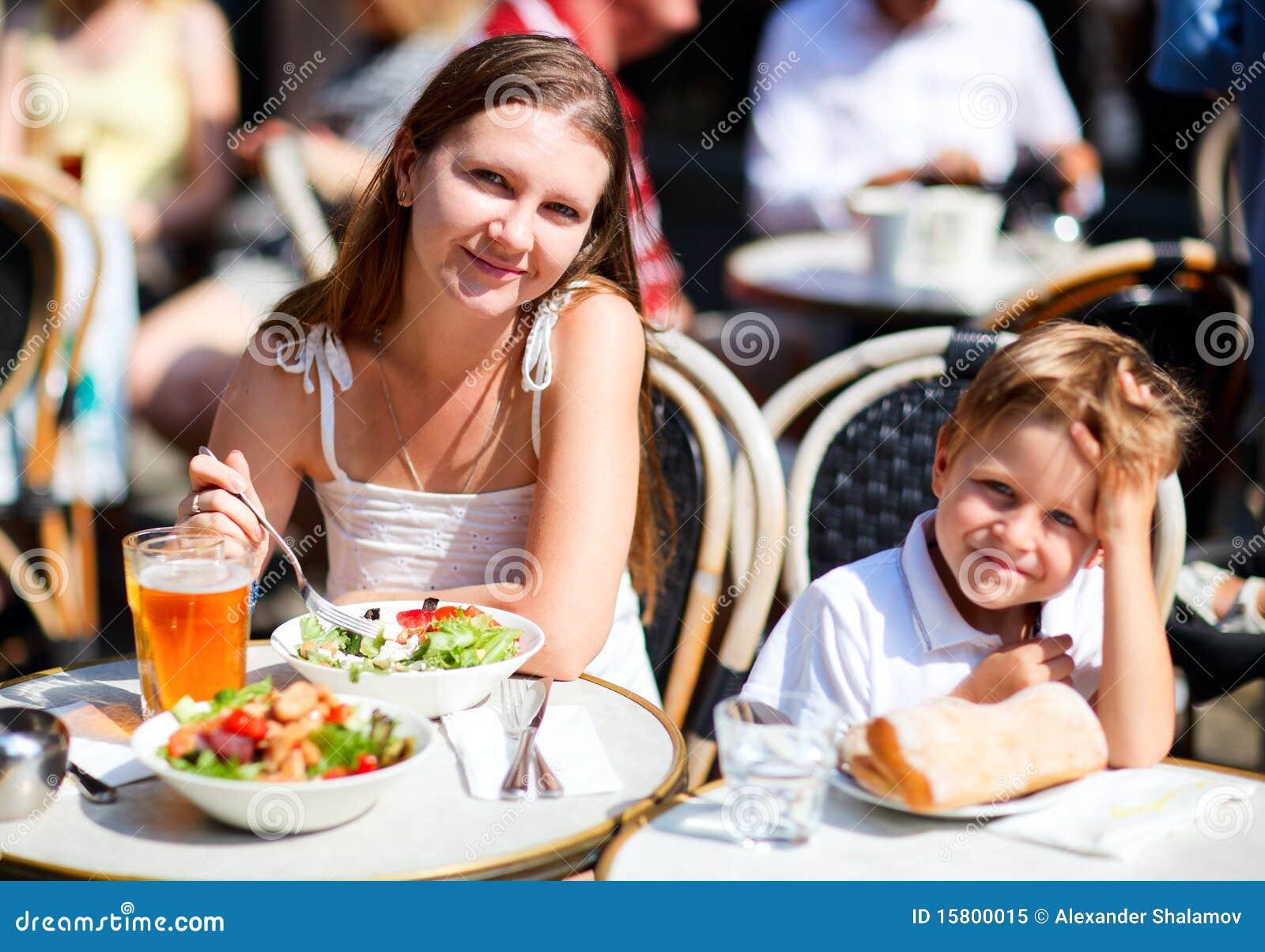 Moeder en zoon die lunch in stoeprestaurant hebben