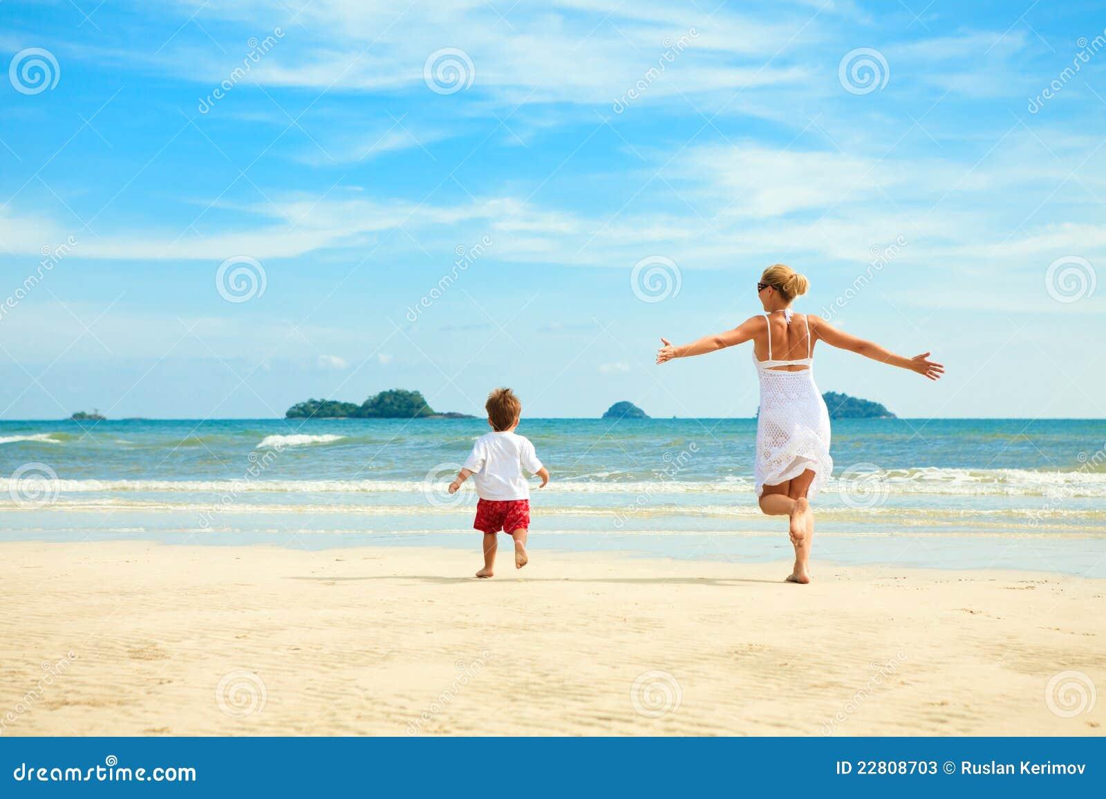 Moeder en zoon die op strand lopen
