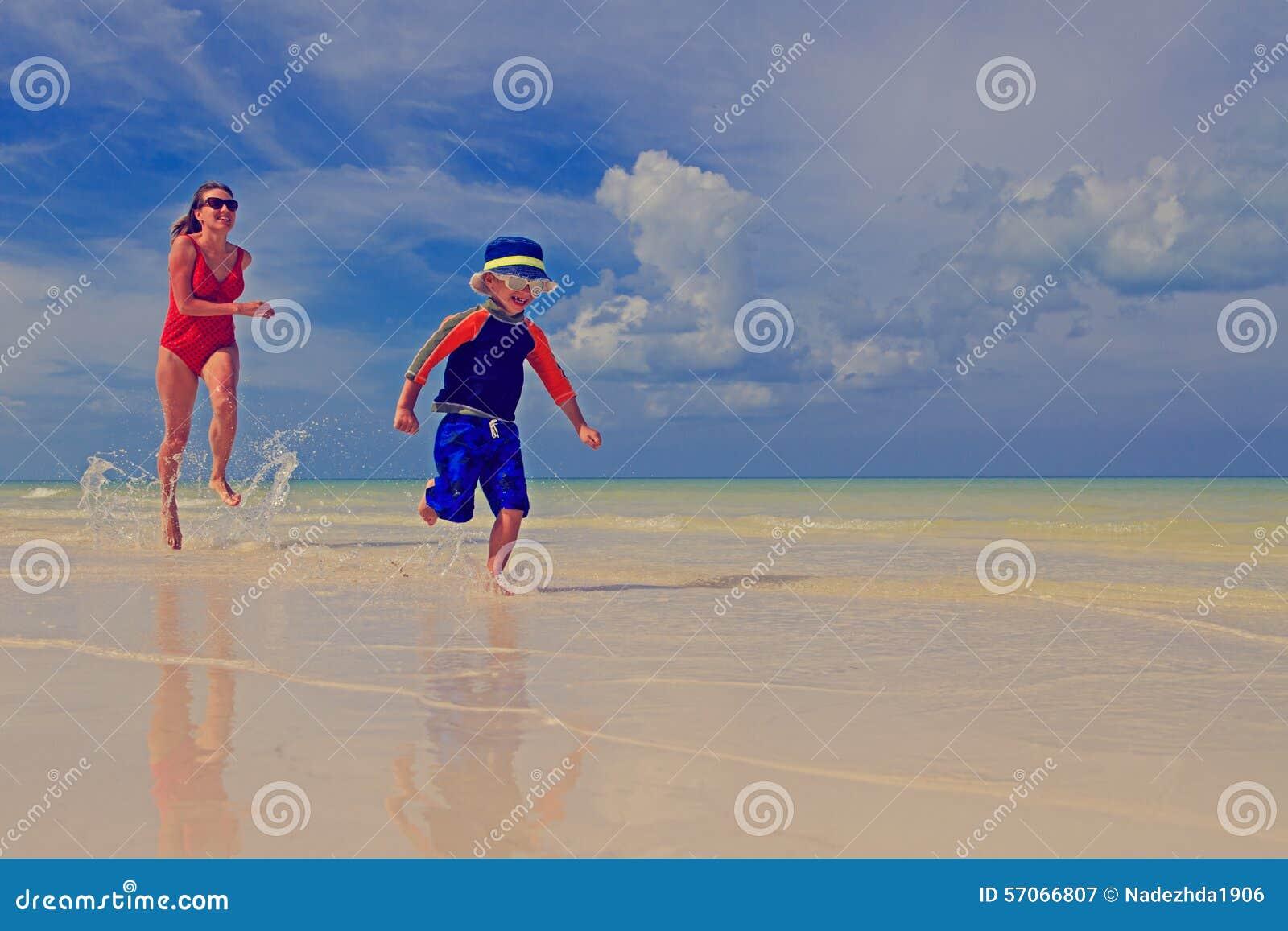Moeder en zoon die op tropisch strand lopen