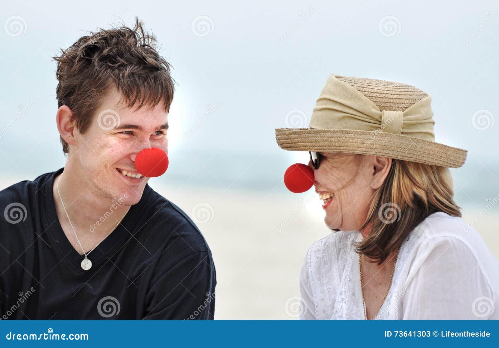Moeder en zoon die pret het lachen het vieren rode neusdag op mooie strandvakantie hebben
