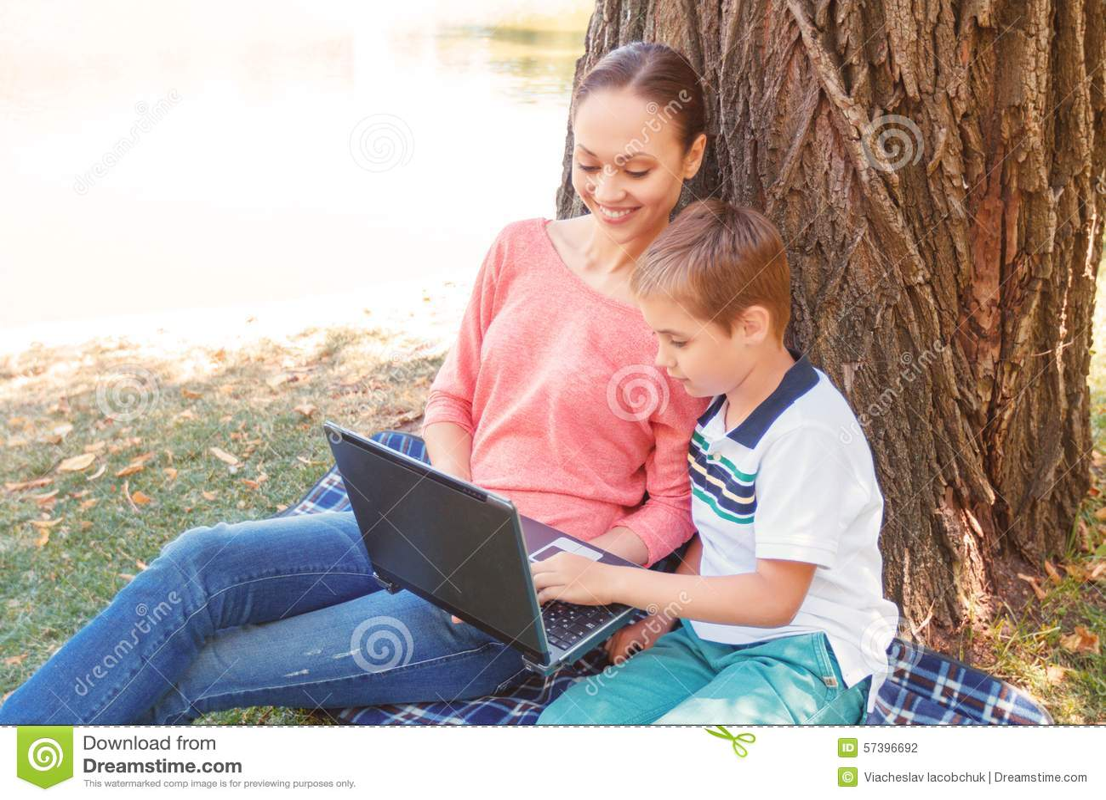 Moeder en zoon met laptop op picknick