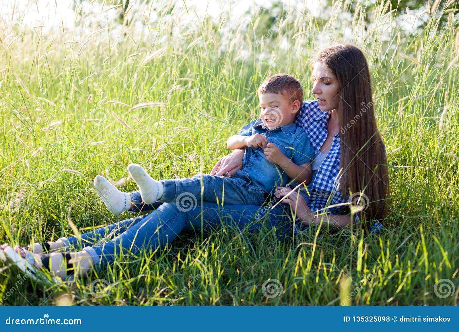 Moeder en zoonsportret tegen groene bomenfamilie