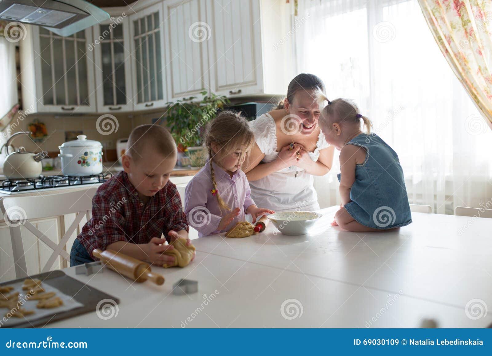 Keuken Voor Kinderen : Moeder met drie kinderen in de keuken die koekjes voorbereiden