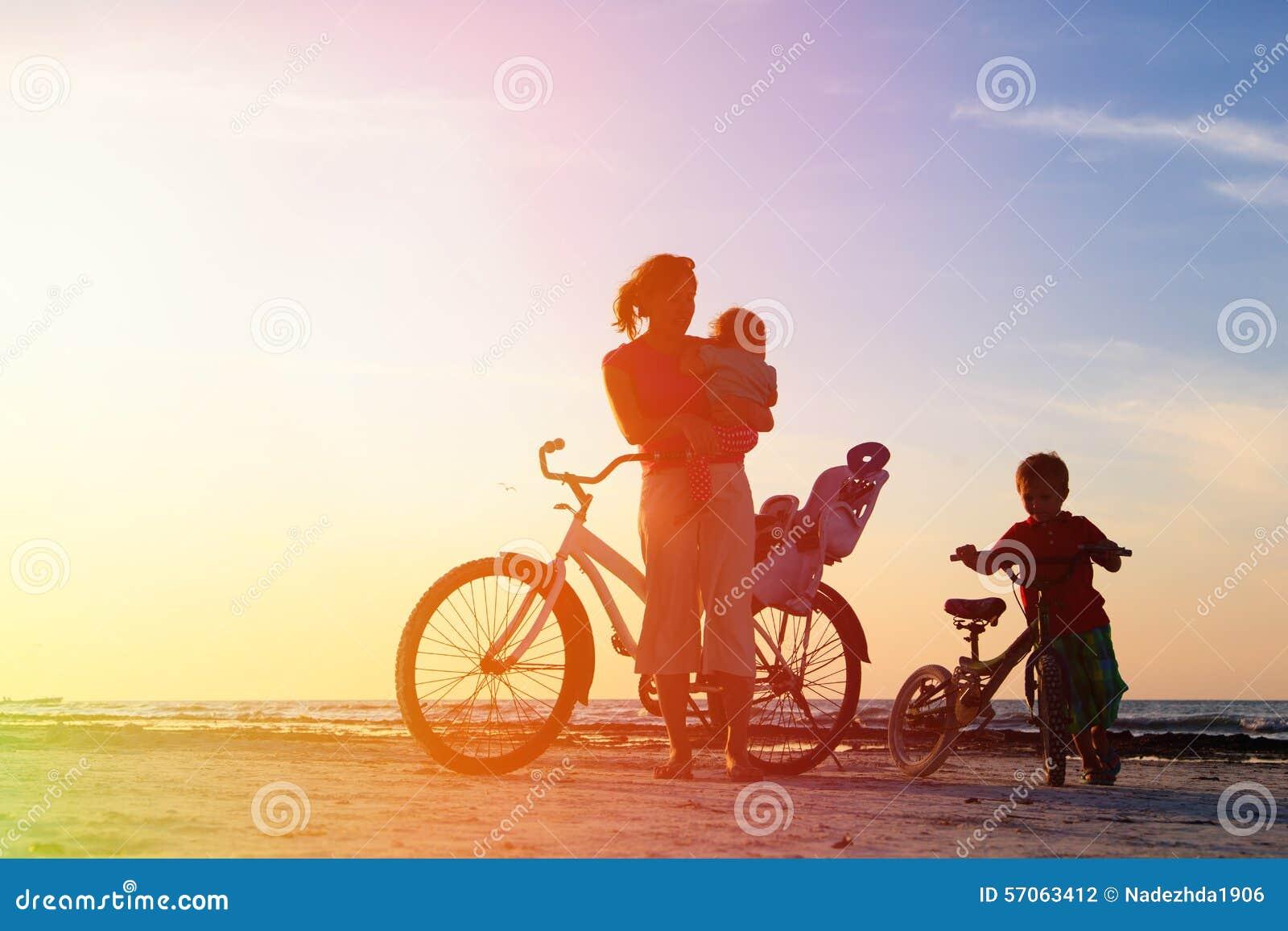 Moeder met jonge geitjes die bij zonsondergang biking